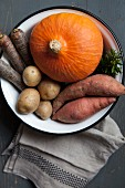 A pumpkin and root vegetables in a bowl