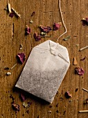 A herb teabag and dried flower petals on a wooden table