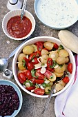 Potato salad with tomatoes, spring onions and basil