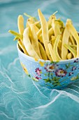Yellow wax beans in floral patterned bowl