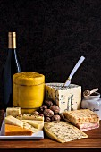 A cheese platter with mustard, walnuts and wine