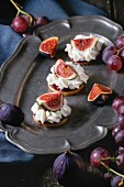 Mini cakes with sliced figs and whipped cream on an old serving platter