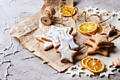 Glazed Christmas star biscuits and dried orange slices on an old newspaper