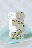 A stack of white nougat with pistachio nuts