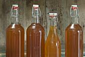 Mehrere Flaschen Apfelsaft mit Bügelverschluss in einem rustikalen Schrankfach