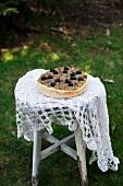 Pissaladiere (Pizza mit karamellisierten Zwiebeln, Sardellen und schwarzen Oliven, Frankreich) auf altem Gartenstuhl