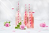 Bottles of homemade rose lemonade with straws