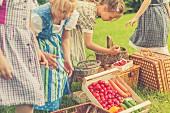 Mädchen in Trachtenkleidern mit frisch geerntetem Obst & Gemüse auf Wiese