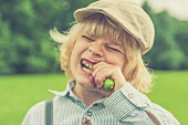 A blond boy wearing a hat biting into a cucumber