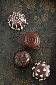 Four chocolate marshmallows decorated with icing (seen from above)