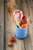 Strawberry ice cream with strawberry sauce and chopped hazelnuts in an ice cream cone