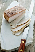 A slice of lardo di colonnata from Italy on a marble platter