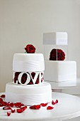 Two wedding cakes with decorated with red roses