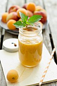 A peach and apricot smoothie in a jar