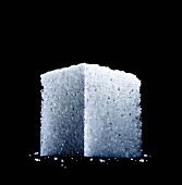A sugar cube against a black background (close-up, seen from below)