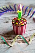 Geburtstagesmuffin verziert mit Schokolinsen & Geburtstagskerze