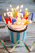 A birthday muffin decorated with burning candles