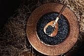 Black rice in a copper dish with a wooden spoon seen from above