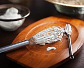 Two whisks with freshly whipped cream on a wooden board