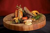 Holzteller mit verschiedenen Würsten, Kräutern, Pilzen und Senf