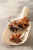 Anise stars on a wooden scoop (close-up)
