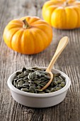 A dish of pumpkin seeds with a spoon