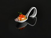 A buckwheat blini and keta caviar on a tasting spoon