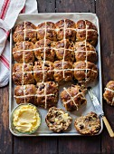 Hot cross buns on a baking tray with butter