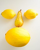A face made of yellow fruits on a white surface