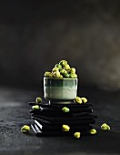 Green Oriental snacks in a bowl on a stack of slate coasters