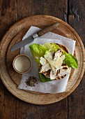 Toast topped with grilled chicken, lettuce and shaved Parmesan