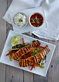 Grilled salmon on a bed of vegetables with rice and a chilli and coriander sauce