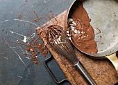 Geschmolzene Milchschokolade mit Schneebesen und Kasserolle