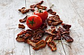 Fresh and dried tomatoes on a wooden surface