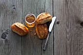 Three rolls, a knife and a jar of honey on a wooden surface