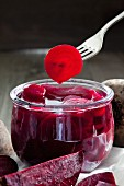 Pickled beetroot in a preserving jar and on a fork
