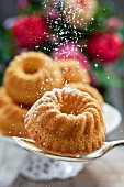 A mini Bundt cake on a spoon being dusted with icing sugar