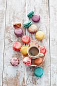 A cup of coffee surrounded by a variety of colourful macaroons