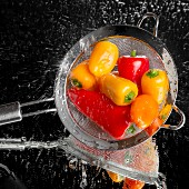 Mini peppers being washed in a sieve