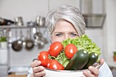A middle-aged woman holding a colander of fresh vegetables