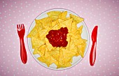 Tortilla chips with salsa on a plate with plastic cutlery (seen from above)
