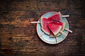 Watermelon ice cream sticks on a plate on a wooden surface (seen from above)