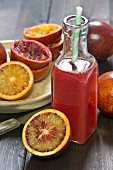 Blood orange juice in a glass bottle with a straw