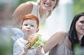 A young red-haired boy holding a sandwich surrounded by his family