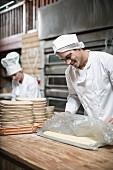 Bäcker in Backstube beim Zubereiten von Teig