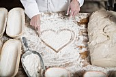 A baker drawing a heart on a floured work surface between baking baskets and dough
