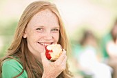 A teenager with red hair eating an apple