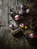 Plums and coffee beans on a wooden chopping board