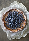 Blueberry tart on a piece of crumpled paper (seen from above)