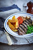 Grilled beef steak with potato wedges and peas